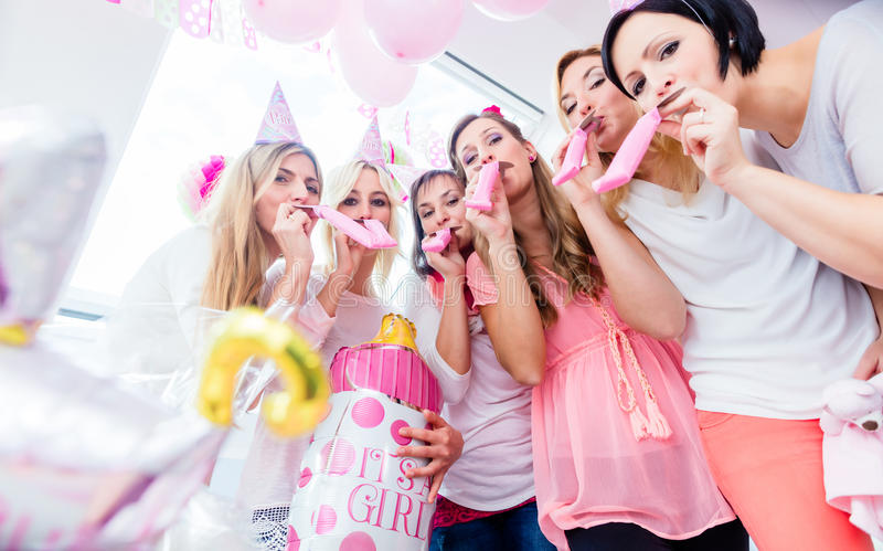 Group of women on baby shower party having fun. Wearing party hats blowing paper streamer stock photo