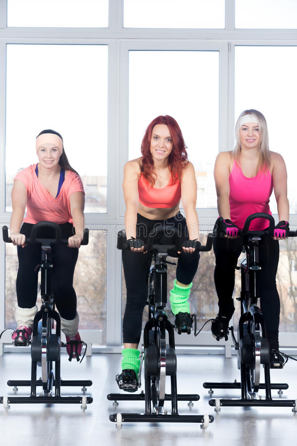 Group of women cycling in gym stock image