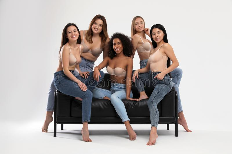 Group of women with different body types in jeans and underwear on sofa against background. Group of women with different body types in jeans and underwear on royalty free stock photography
