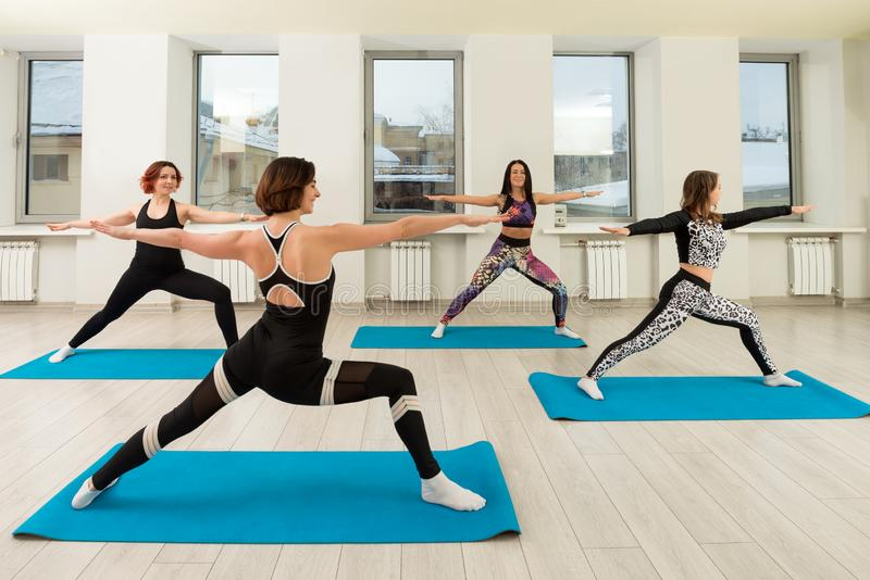 Group of women doing yoga in a gym view stock photos