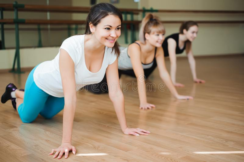 Group women on floor of sports gym doing push ups. Fitness club stock images