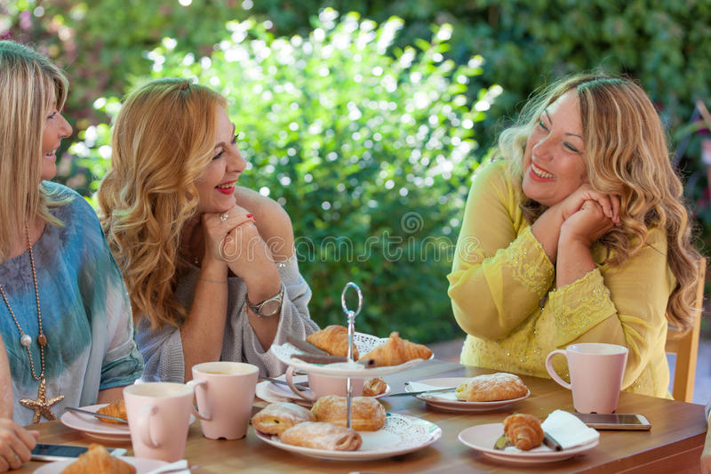 Group women friends meeting for coffee and cakes. royalty free stock photo