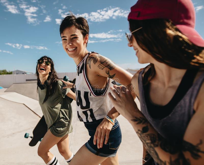 Women friends running outdoors at skate park stock photography