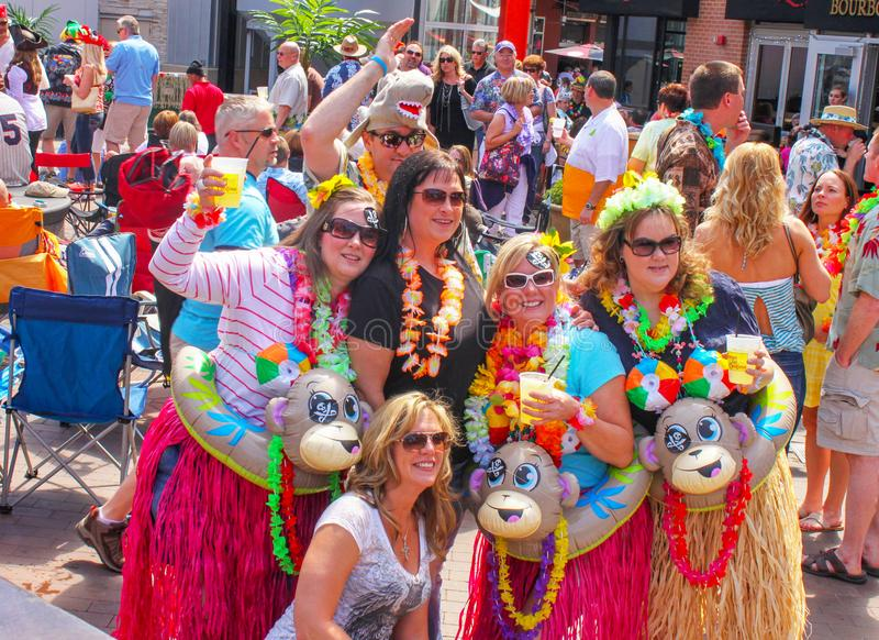 Group of women in front of crowd posing for picture before a Jimmy Buffet concert with silly tropical costumes grass skirts and dr stock image