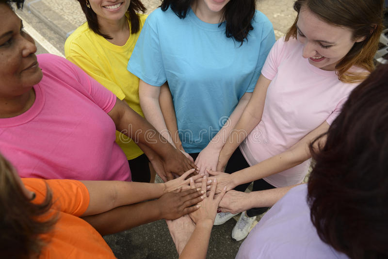 Group of women with hands together stock photos