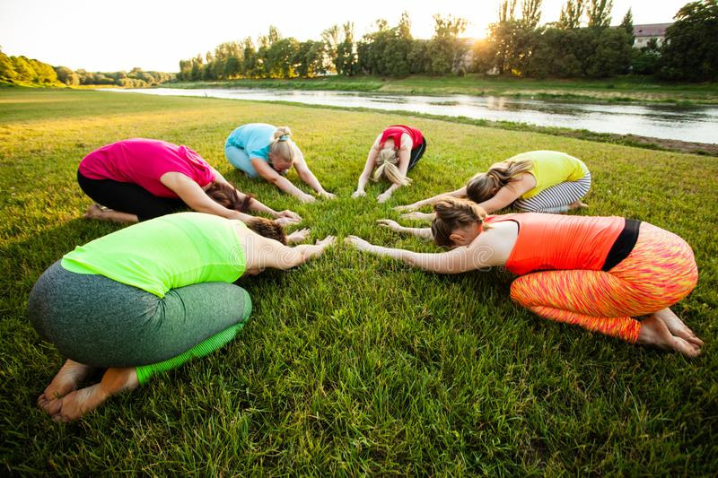 Group of women laying on a grass while practicing yoga royalty free stock photo