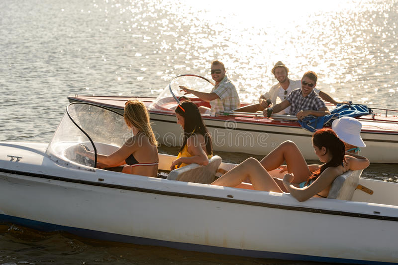 Young people driving motorboats summer lake stock images