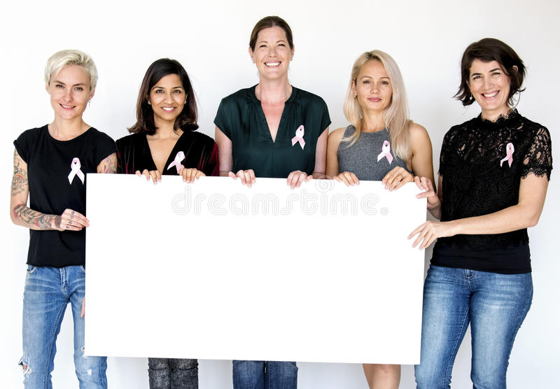 Group of women with pink ribbon and holding blank banner for breast cancer awareness royalty free stock images