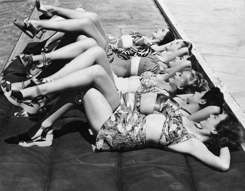 Group of women relaxing in a row together stock images