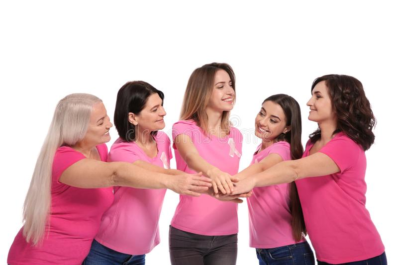 Group of women with silk ribbons joining hands on white. Breast cancer awareness concept. Group of women with silk ribbons joining hands on white background royalty free stock images