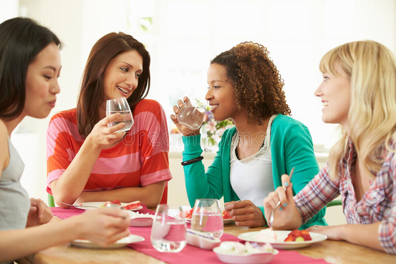 Group Of Women Sitting Around Table Eating Dessert. Talking To Each Other Holding Glass Of Water