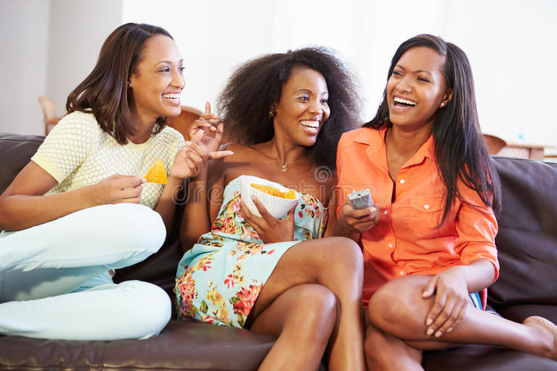 Group Of Women Sitting On Sofa Watching TV Together royalty free stock images