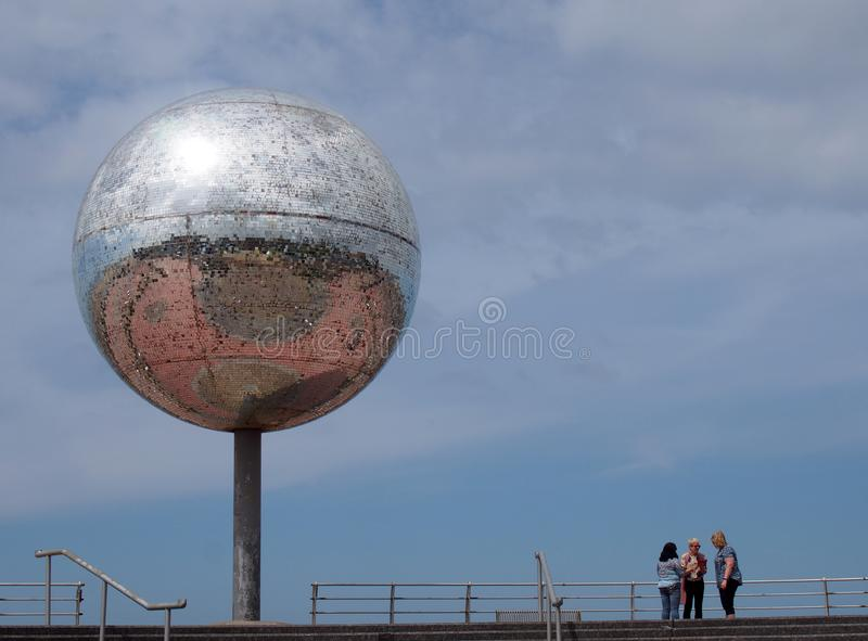 A group of women stood near the giant glitter ball on blackpool promenade with blue sky and reflection of the town in the mirrored stock photos
