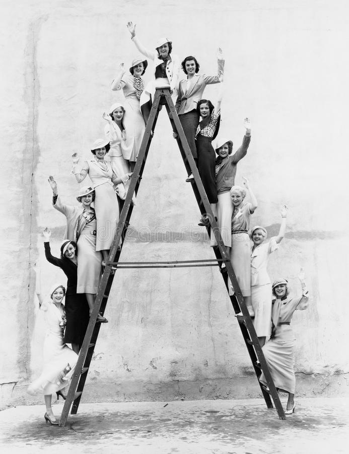 Group of women on tall ladder. (All persons depicted are no longer living and no estate exists. Supplier grants that there will be no model release issues stock photos