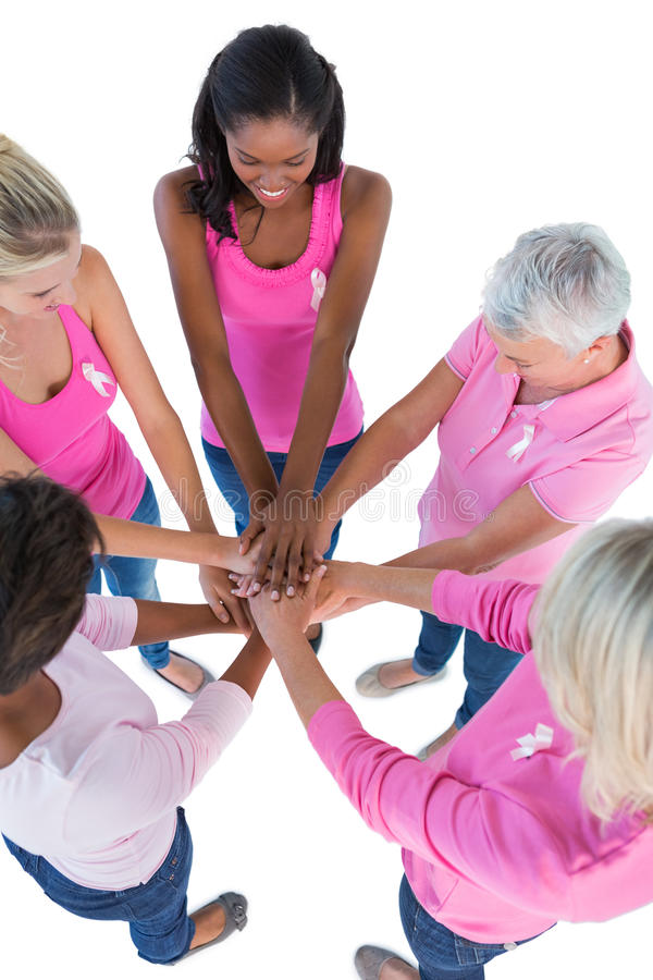 Group of women wearing pink and ribbons for breast cancer putting hands together royalty free stock photography