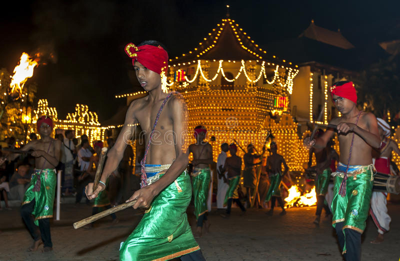 A group of Wood Tappers perform in front of the Temple of the Sacred Tooth Relic during the Esala Perahera in Kandy, Sri Lanka. Wood Tappers perform a dance stock image