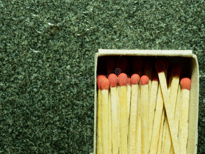 A group of wooden match sticks with red head in match box over black or dark granite texture royalty free stock photo