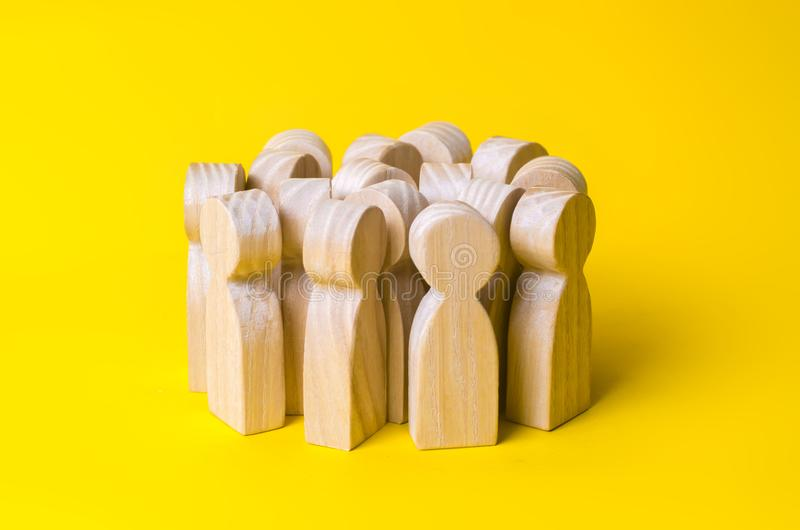 Group of wooden people figurines on a yellow background. Crowd,. Meeting, social activity. Society, social group. Herd instinct, management of people. Human stock image