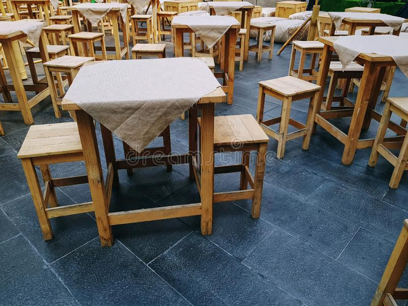 Group of Wooden Table with Cloth Covers and Chairs at Outdoor Street Food Restaurant. Large Group of Wooden Table with Cloth Covers and Chairs at Outdoor Street stock photo