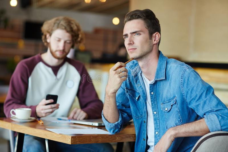 Group Work on Start-up Project. Handsome young manager looking away pensively while sitting at cafe table with his bearded colleague and working on start-up stock image