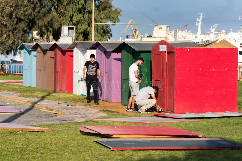 A group of workers - carpenters building plywood cabins with battery drills outdoors on a grass in Heraklion, Greece stock image