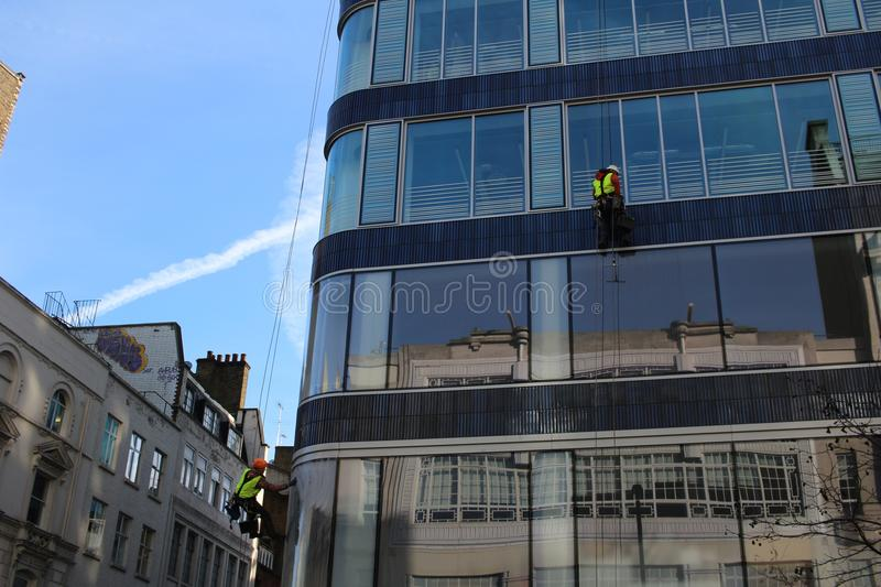 A group of workers cleaning washing windows on high rise building. stock photography