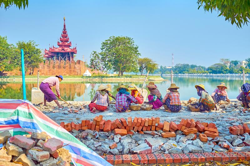The group of workers in Mandalay, Myanmar. MANDALAY, MYANMAR - FEBRUARY 23, 2018: Burmese women during manual construction works on embankment of the Citadel`s royalty free stock photography