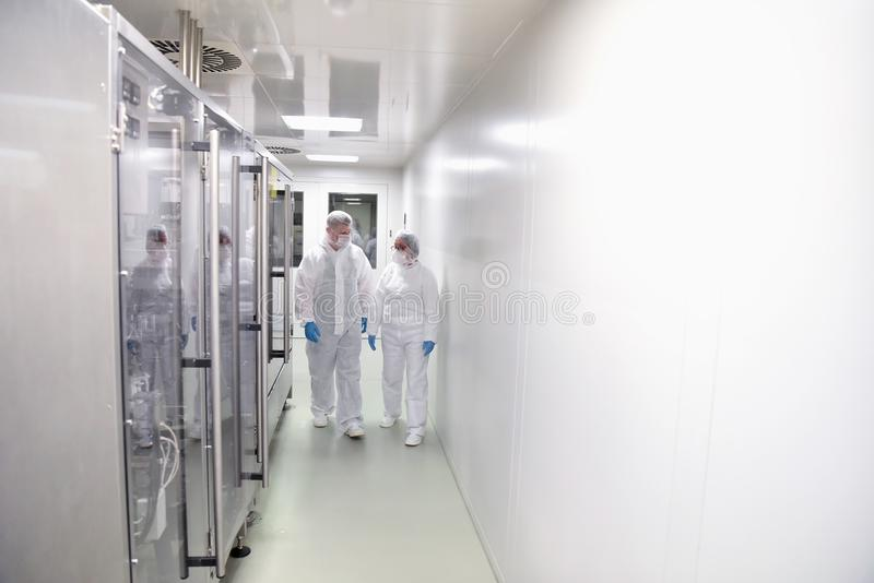 Group of workers in protective clothing in a sterile room of a f royalty free stock images