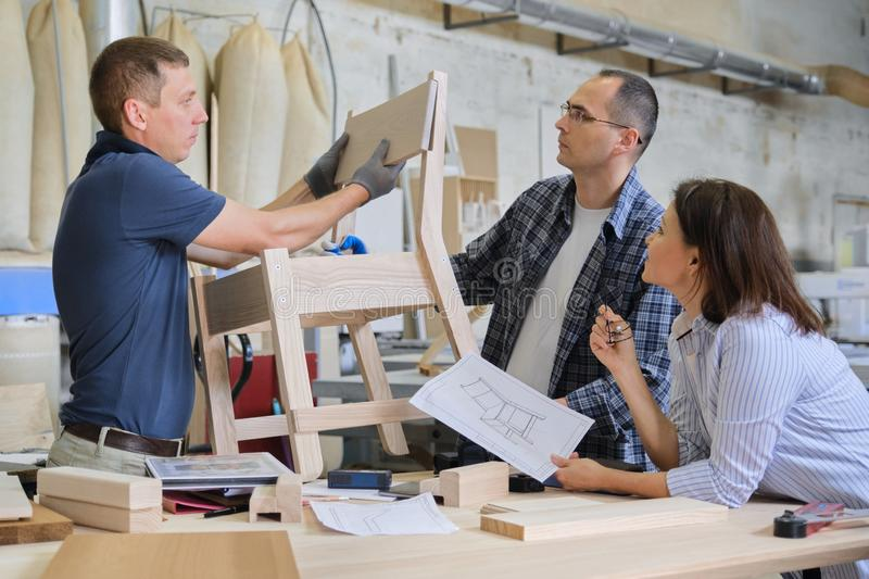 Group of working designers in carpentry workshop. Group of working designers discussing production of new model of wooden modern chair, background carpentry royalty free stock photo