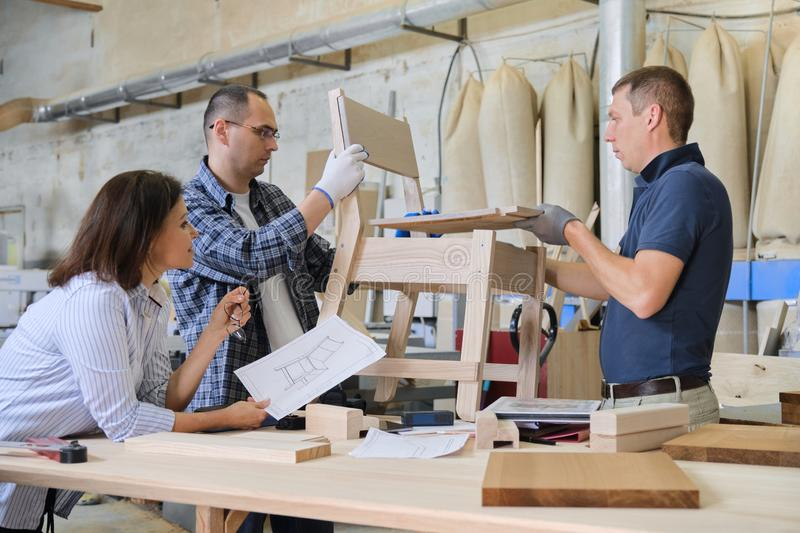 Group of working designers in carpentry workshop. Group of working designers discussing production of new model of wooden modern chair, background carpentry stock images