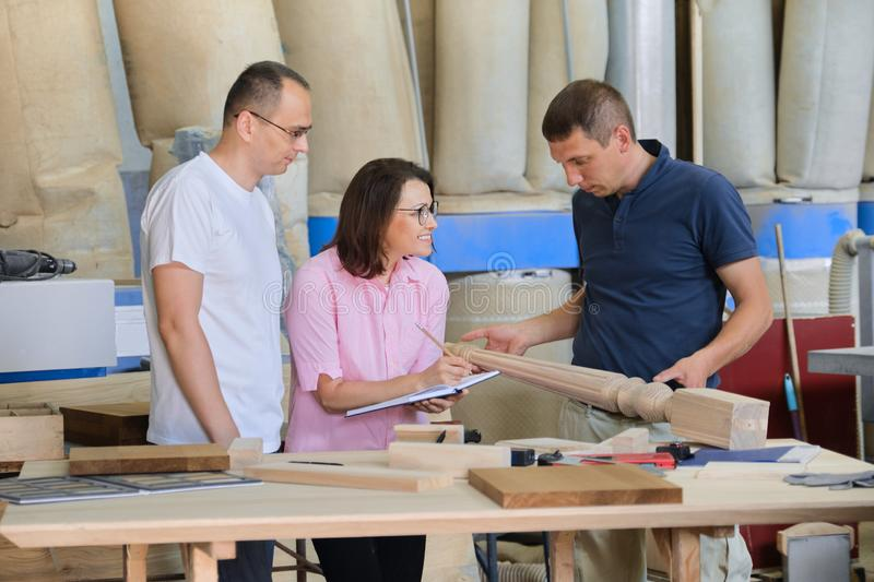 Group of working people discussing wood products. Group of working people discussing work process, wood products in carpentry workshop royalty free stock photography