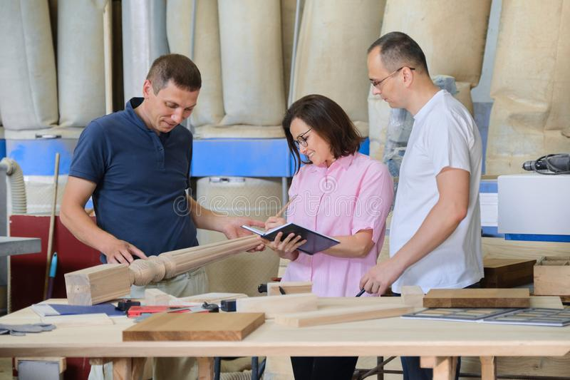 Group of working people discussing wood products. Group of working people discussing work process, wood products in carpentry workshop stock images