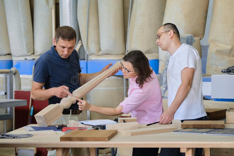 Group of working people discussing wood products. Group of working people discussing work process, wood products in carpentry workshop royalty free stock images