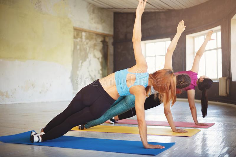 Group of women doing side plank static exercise. Group workout, activity, healthy lifestyle, sport, weight loss. Women yoga class in gym. Sportswomen doing side royalty free stock photos