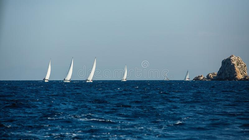 Group yacht boats with white sails near the rocks in the Aegean sea. stock photos
