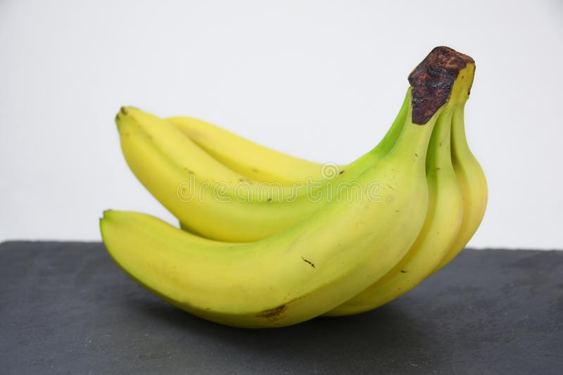 Bunch of bananas on black slate table. Group of yellow banana`s on dark black slate table. Healthy fruit. Vitamines a b c d royalty free stock photography