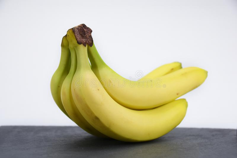 Bunch of yellow bananas on dark slate. Group of yellow banana`s on dark black slate table. Healthy fruit. Vitamines a b c d royalty free stock images