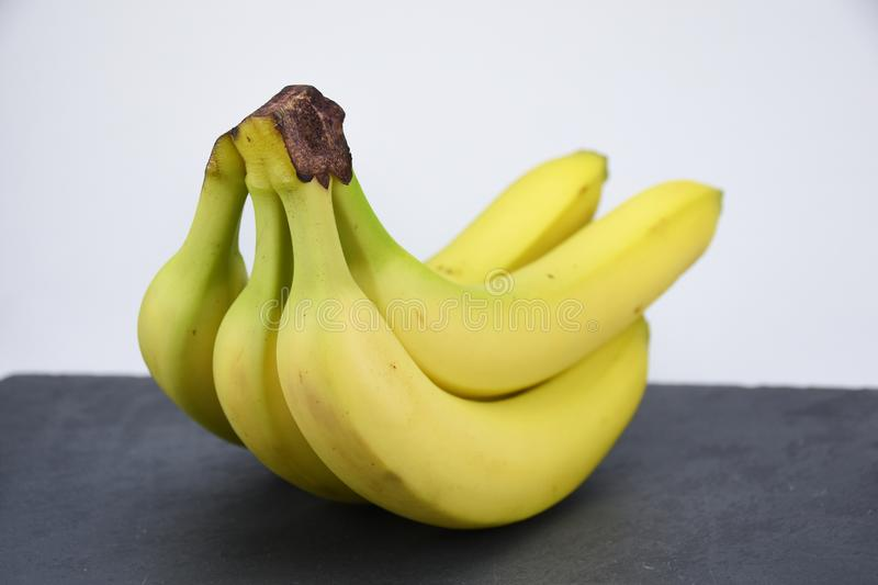 Bunch of yellow bananas on dark slate white background. Group of yellow banana`s on dark black slate table. Healthy fruit. Vitamines a b c d stock photo