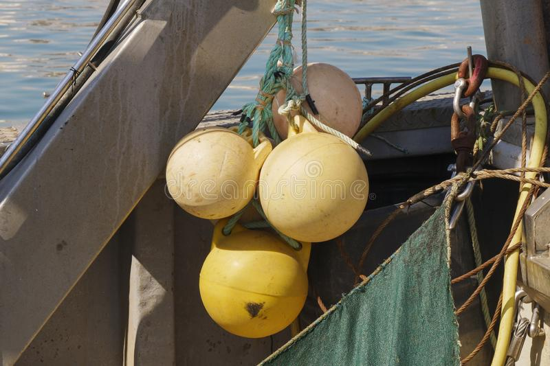 Group of yellow buoys hanging from the board of a fishing ship royalty free stock photo