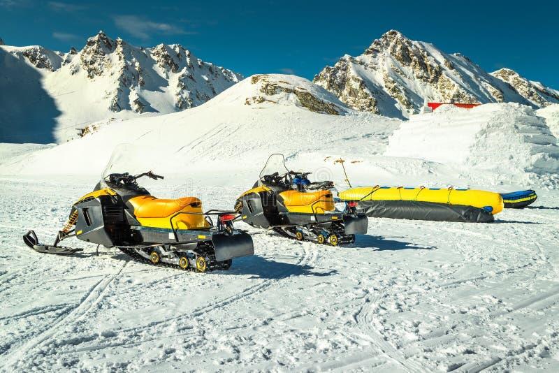 Group of yellow snowmobiles in mountains, Balea lake, Transylvania, Romania royalty free stock photo
