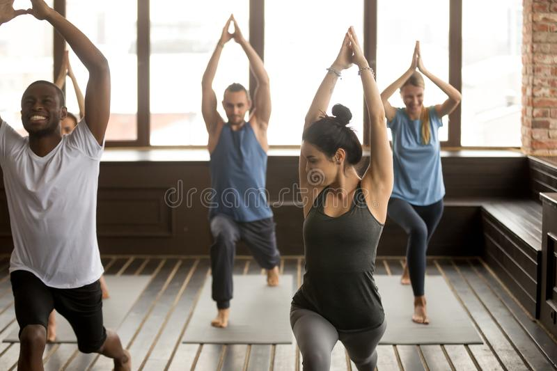 Group yoga in studio, diverse people doing exercises with instru stock image