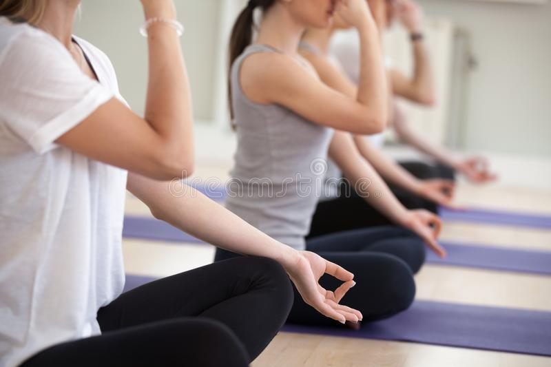 Group of yogi people practicing Alternate Nostril Breathing, clo. Group of young sporty people practicing yoga lesson in gym, doing Alternate Nostril Breathing royalty free stock image
