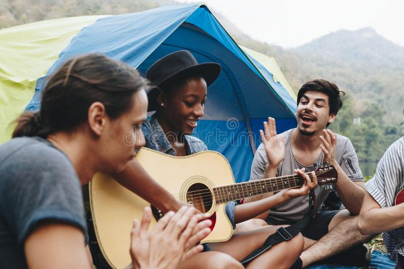 Group of young adult friends in camp site playing guitar stock images