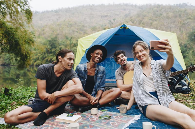 Group of young adult friends in camp site taking a group selfie outdoors recreational leisure, freedom and adventure concept stock photo