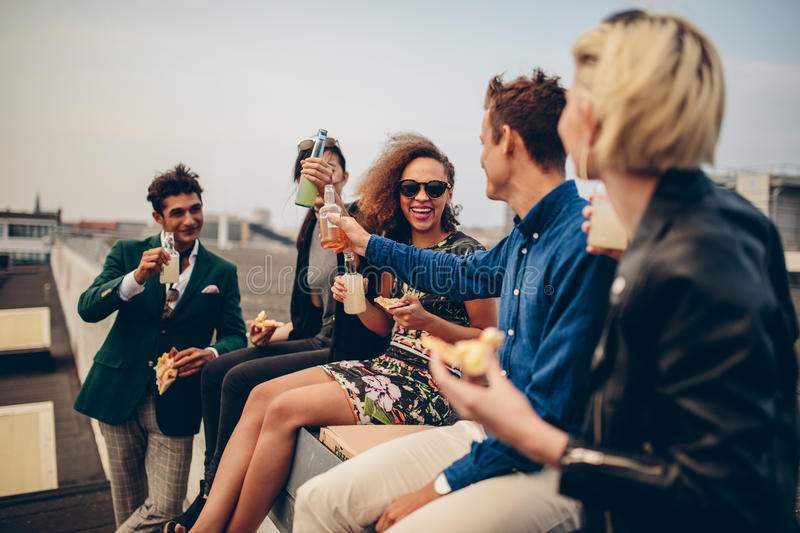 Group of young adults drinking outdoors. Multiethnic group of young friends partying on terrace, drinking and celebrating. Young men and women having drinks on royalty free stock photo