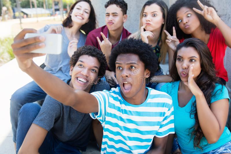 Group of young adults making funny selfie shots with phone. Outdoor in the summer stock photo