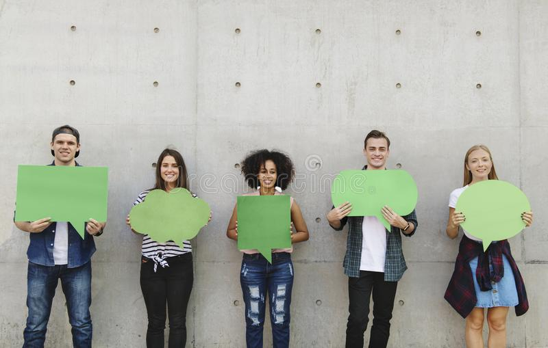 Group of young adults outdoors holding empty placard copyspace t royalty free stock photography