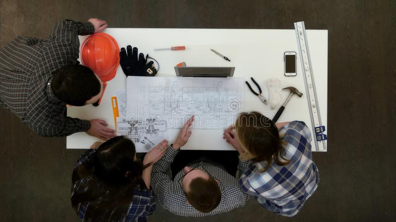 Group of young architects working on drawings royalty free stock photos