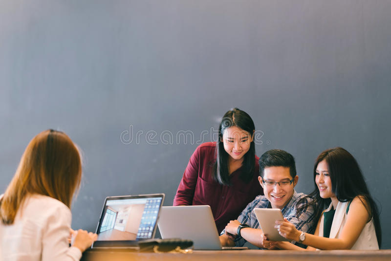 Group of young Asian business colleagues in team casual discussion, startup project business meeting or happy teamwork brainstorm royalty free stock image