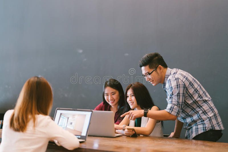 Group of young Asian business colleagues in team casual discussion, startup project business meeting or happy teamwork brainstorm stock photography